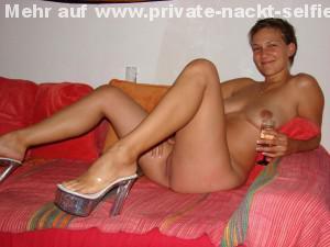 kurzhaarige exfreundin nackt mit einem sektglas auf der couch und laechelt in die kamera